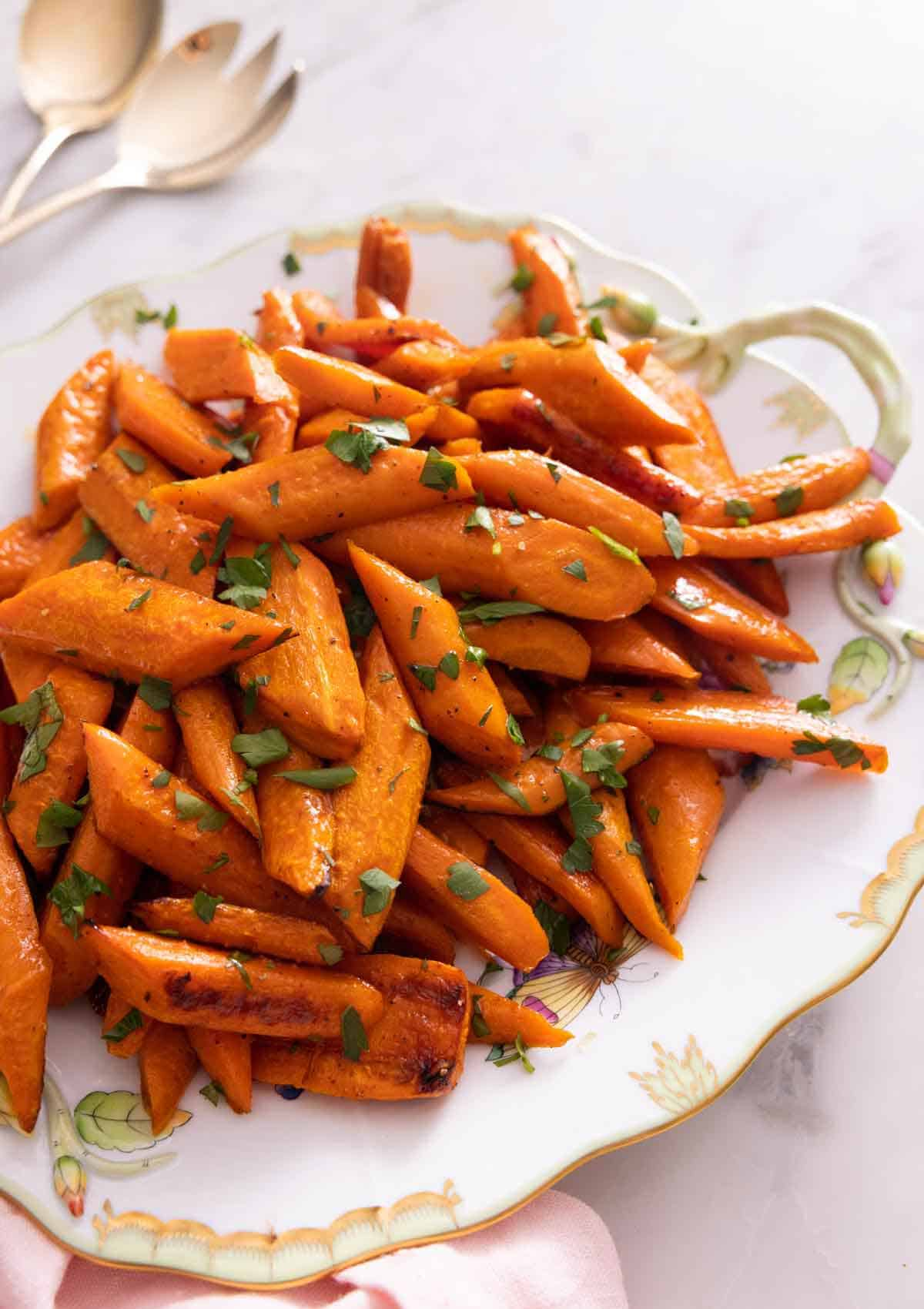 A platter of roasted carrots with parsley on top.