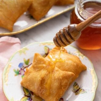 Pinterest graphic of a plate of two sopapillas with honey drizzled over top.