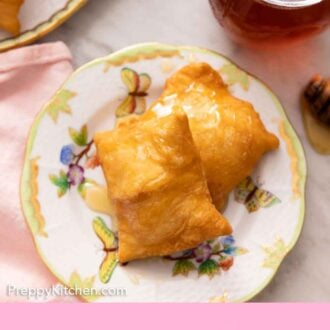 Pinterest graphic of a plate with two sopapillas with honey drizzled on top.