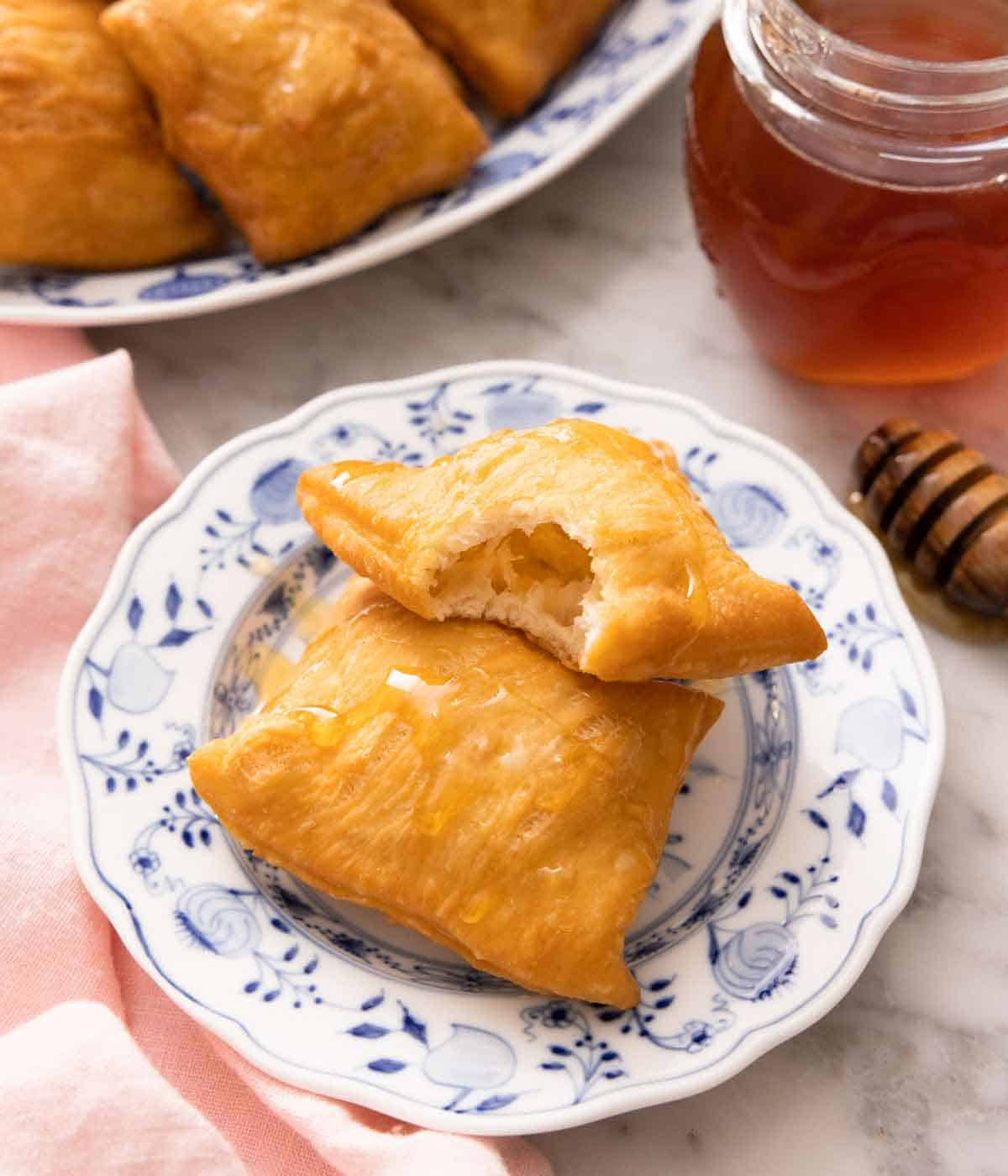 A plate with two sopapillas, one with a bite taken out of it. A jar of honey and more sopapillas in the back.