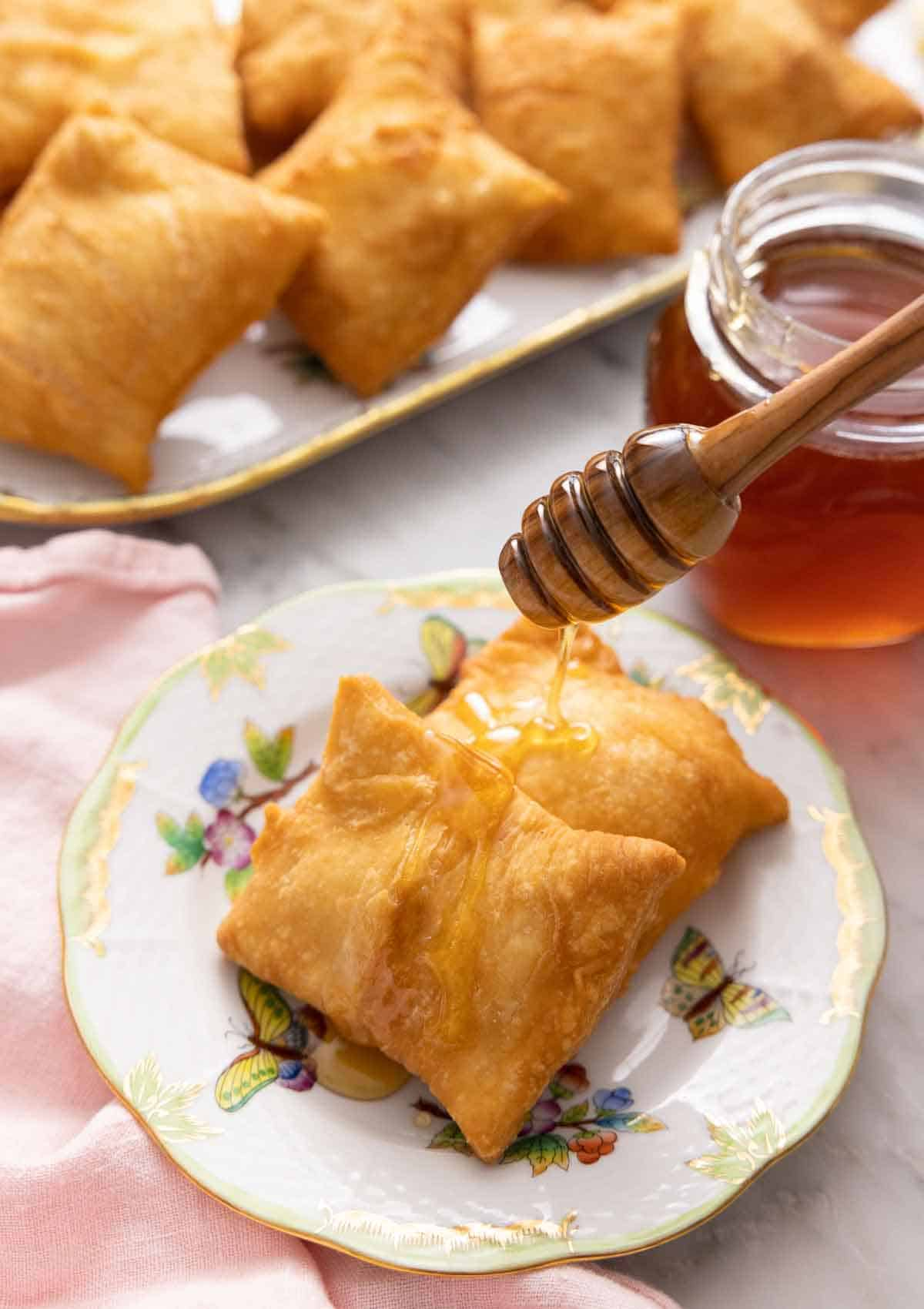 A plate with two sopapillas with honey drizzled over them.