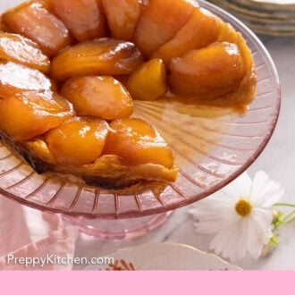 Pinterest graphic of a tarte Tatin with a slice cut out on a pink serving dish.