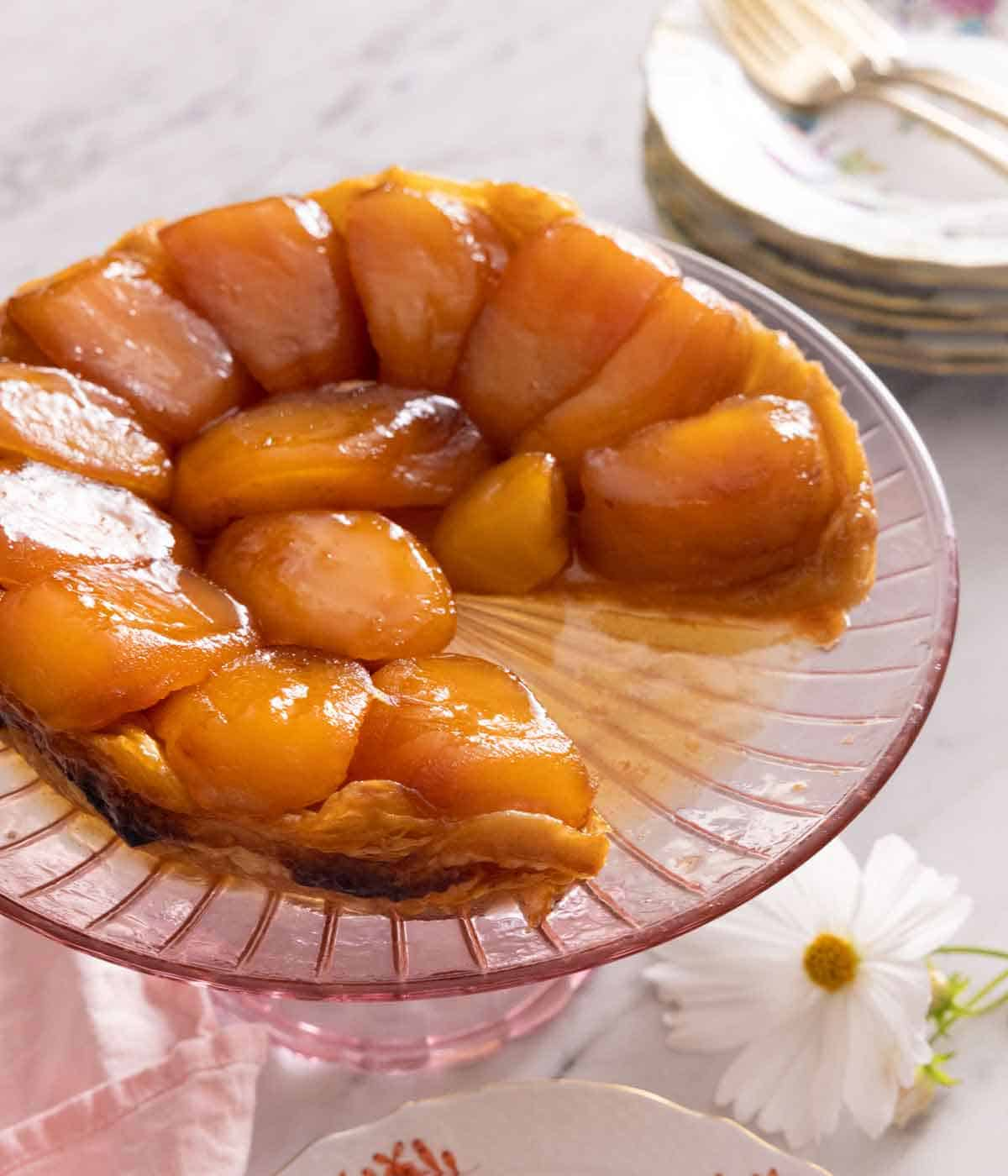 A tarte Tatin with a slice cut out of it on a serving platter.