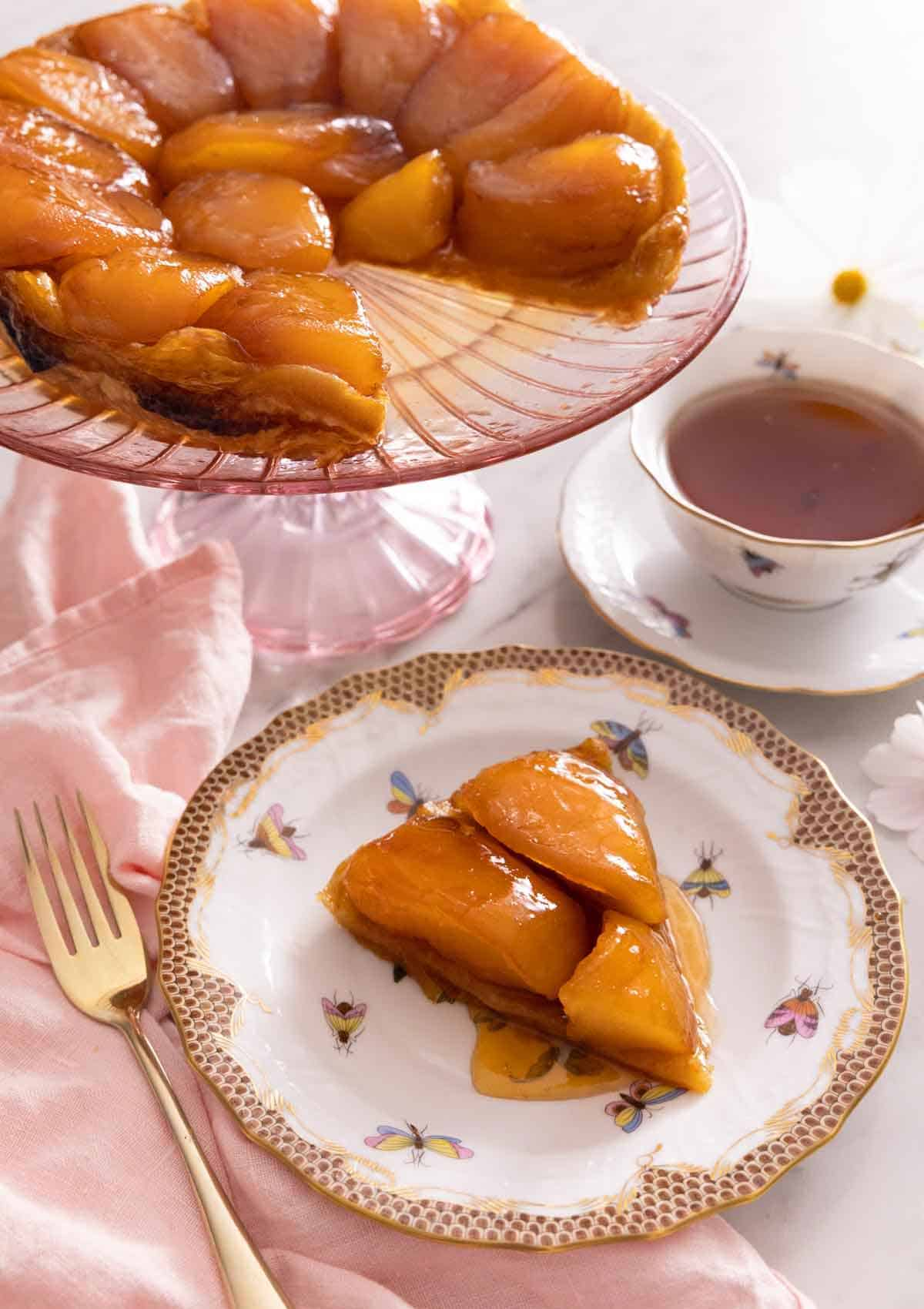 A slice of tarte Tatin on a plate in front of a cake stand with the rest of the Tatin behind it.