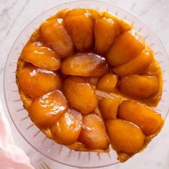 Overhead view of a tarte Tatin with a slice cut and pulled slightly away.
