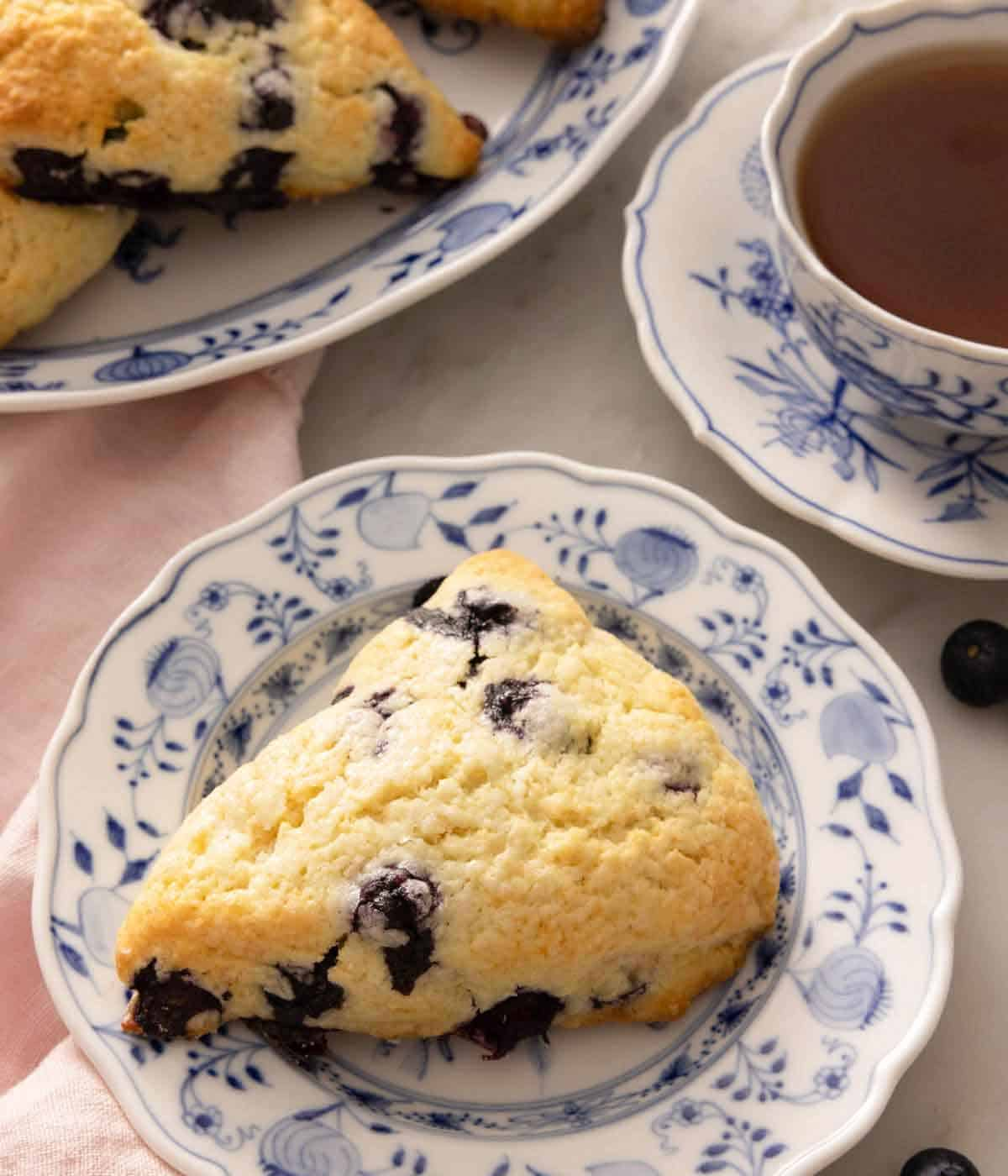 A plate with a blueberry scone in front of a mug of tea.