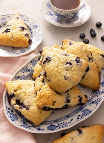 An oval platter of blueberry scones in front of a cup of tea and scattered blueberries on the counter.