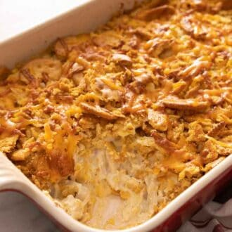 Chicken casserole in a baking dish with a serving scooped out.