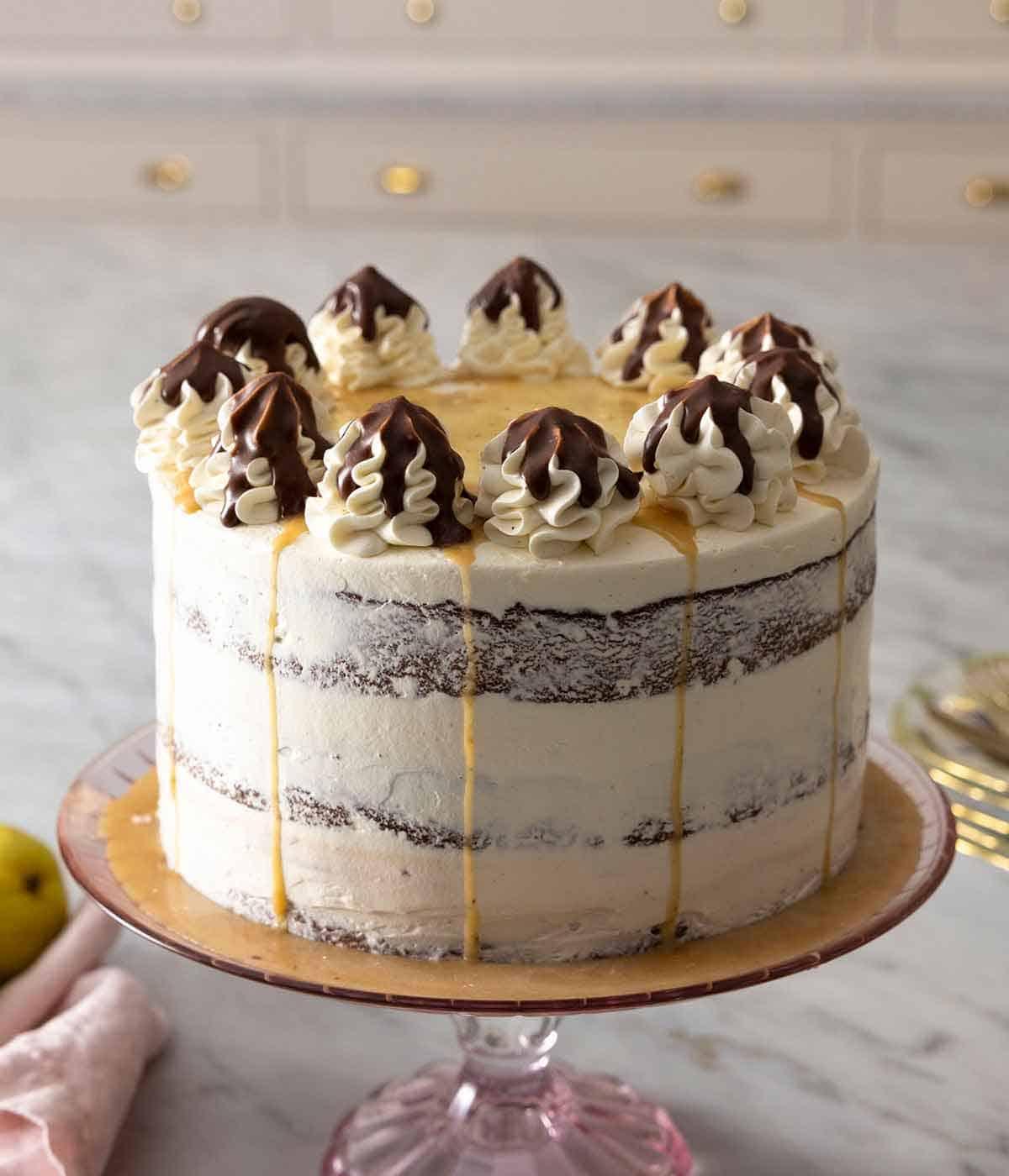 A chocolate pear cake on a cake stand.