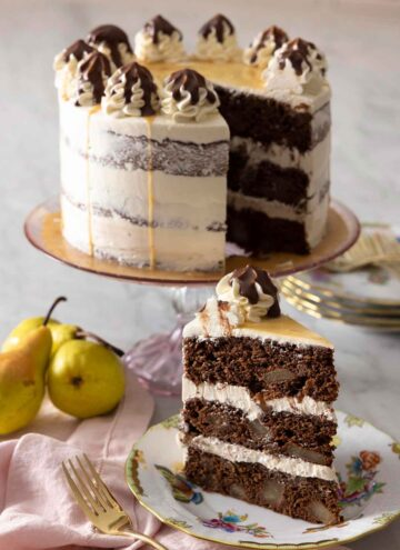A chocolate pear cake on a cake stand with a slice in front.