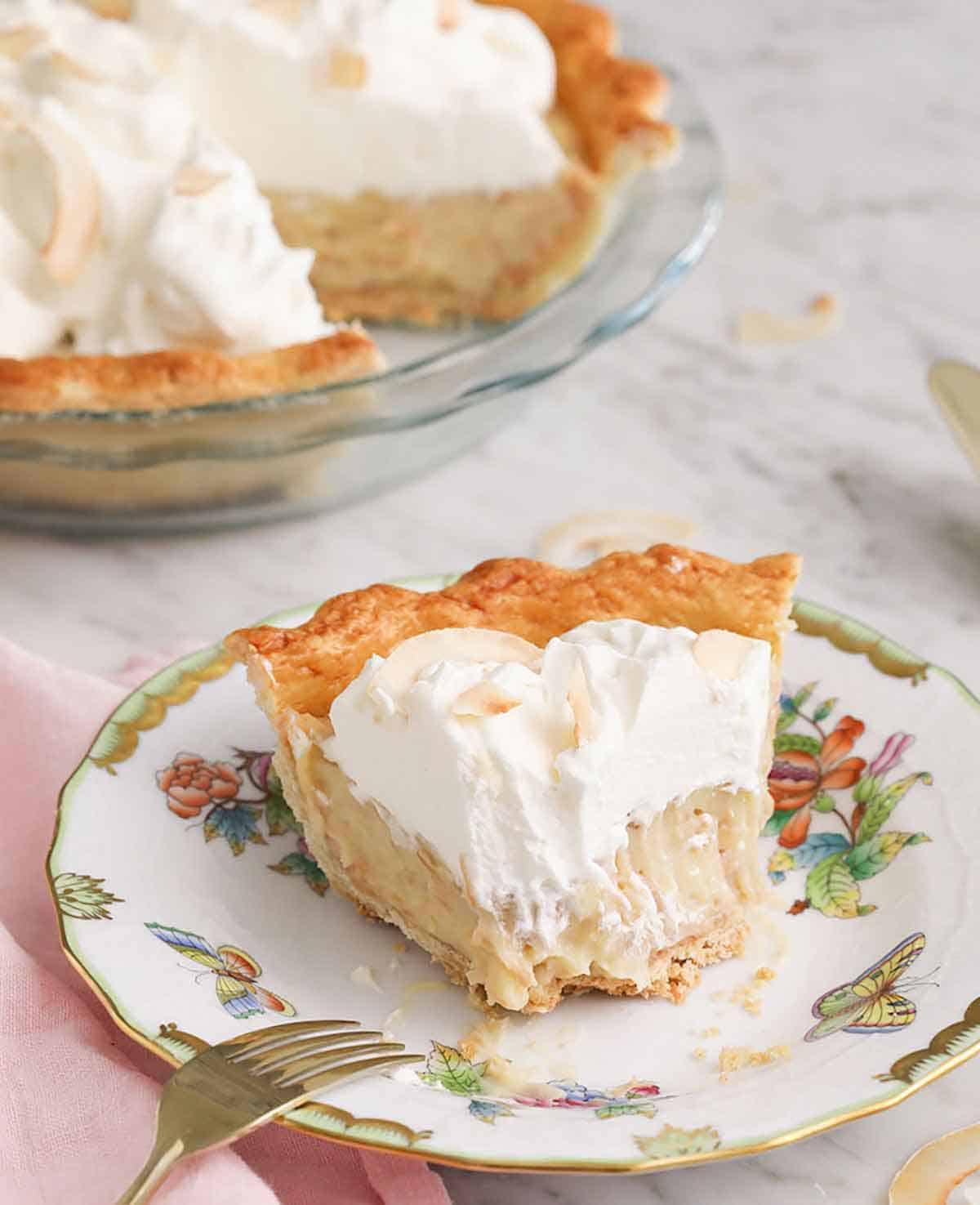 A plate with a slice of coconut cream pie with a bite taken out.