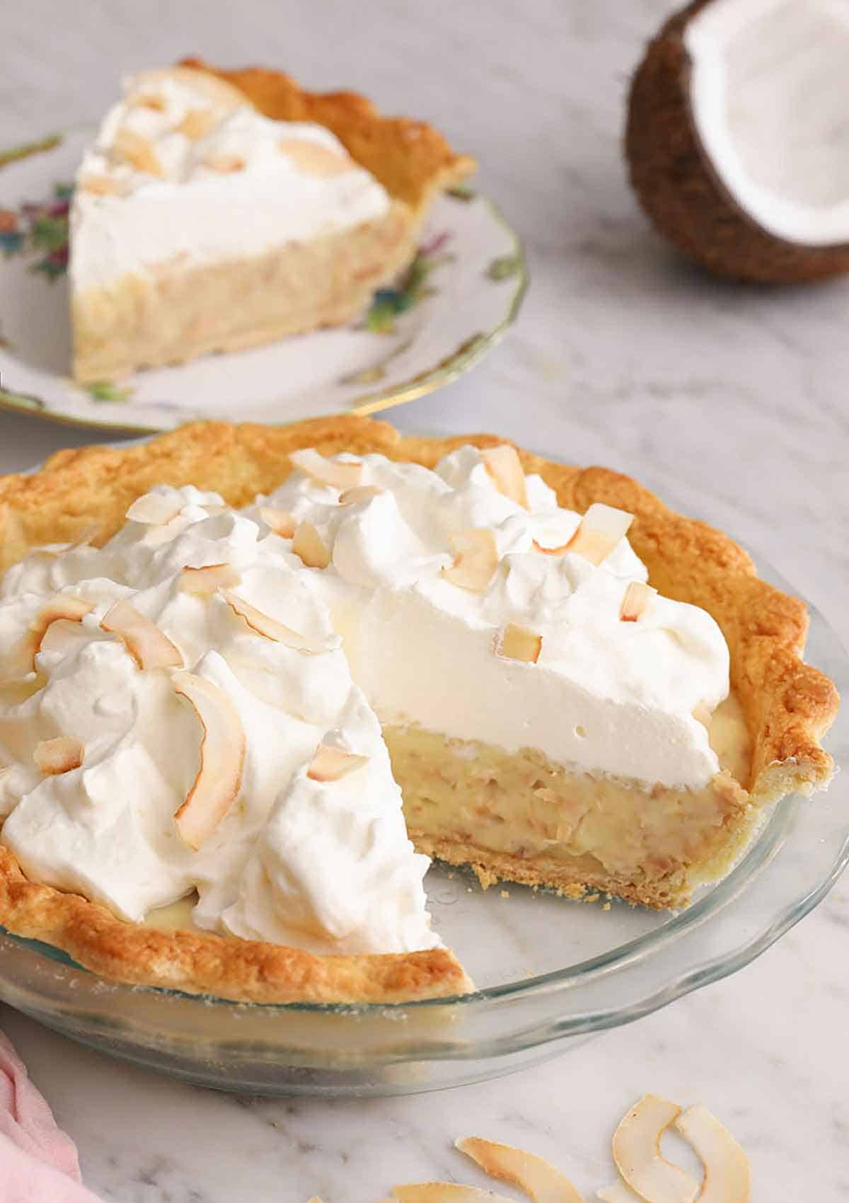 A coconut cream pie in a glass pie dish with a slice cut out.