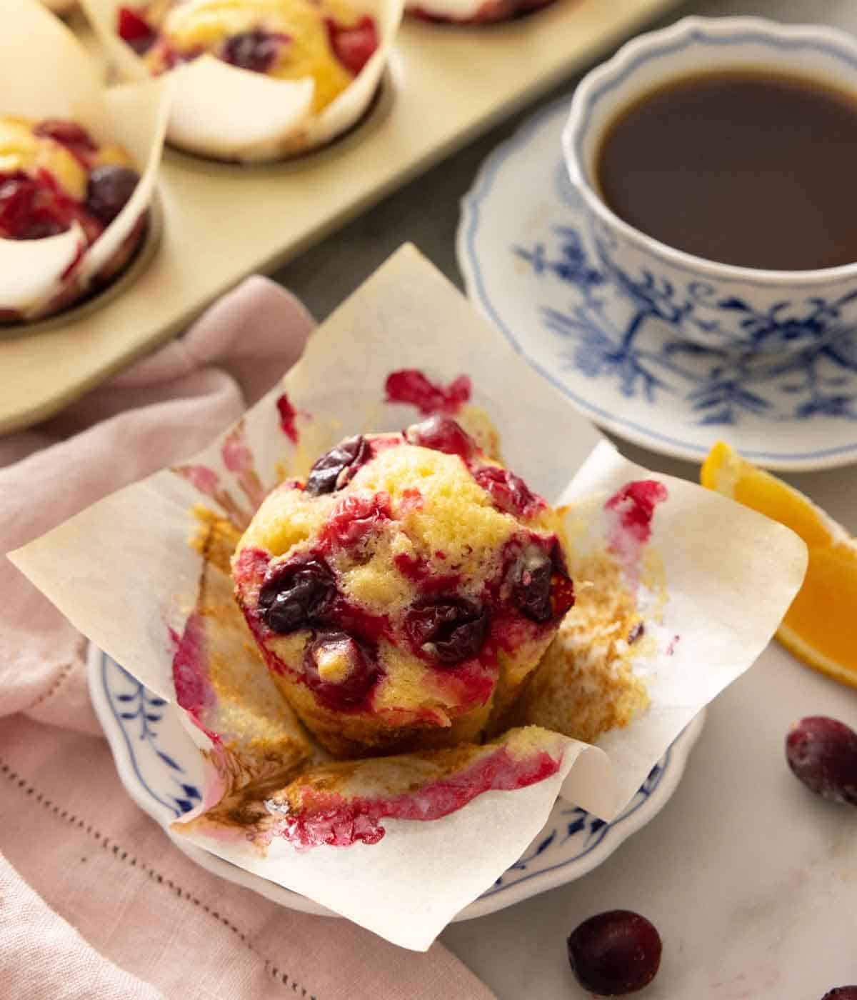 A plate with a cranberry orange muffins with the liner pulled open.