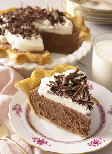 A slice of French silk pie on a plate in front of the rest of the pie.