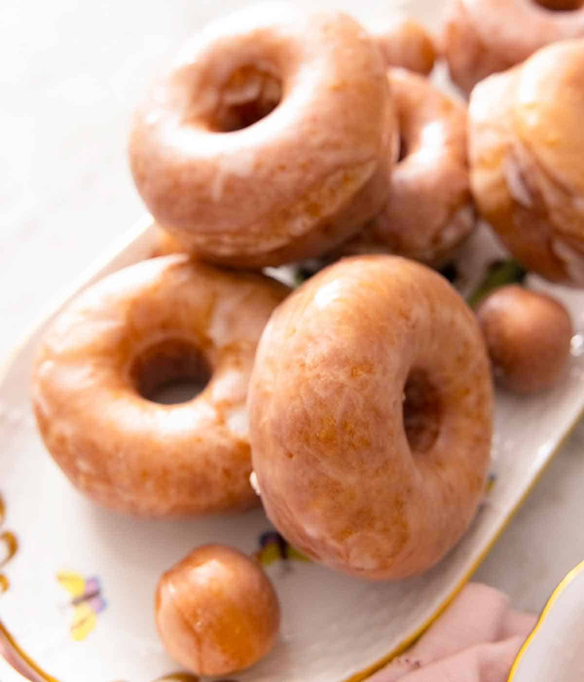 A platter of glazed donuts stacked on top of each other with donut holes.