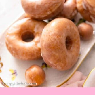 Pinterest graphic of an oval platter of glazed donuts.