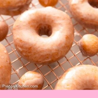Pinterest graphic of glazed donuts and donut holes on a wire rack.