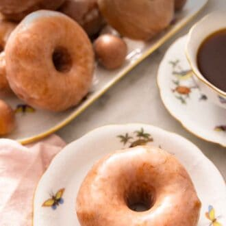 Pinterest graphic of a platter of glazed donuts with a plate in front with one donut.