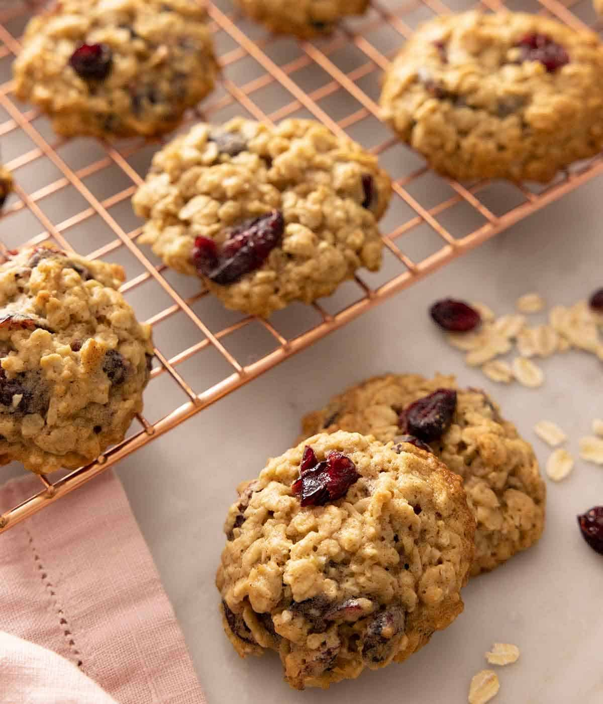 Oatmeal cranberry cookies on a cooling rack and on the counter.