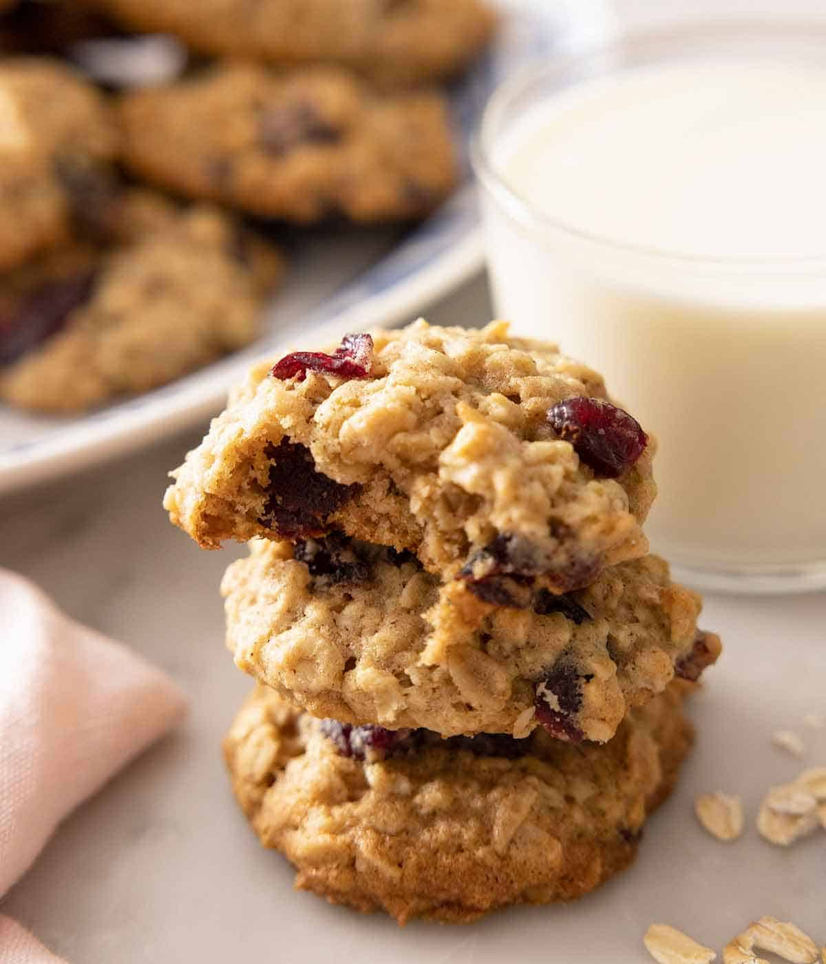 A stack of three oatmeal cranberry cookies with a bite taken from the top cookie.