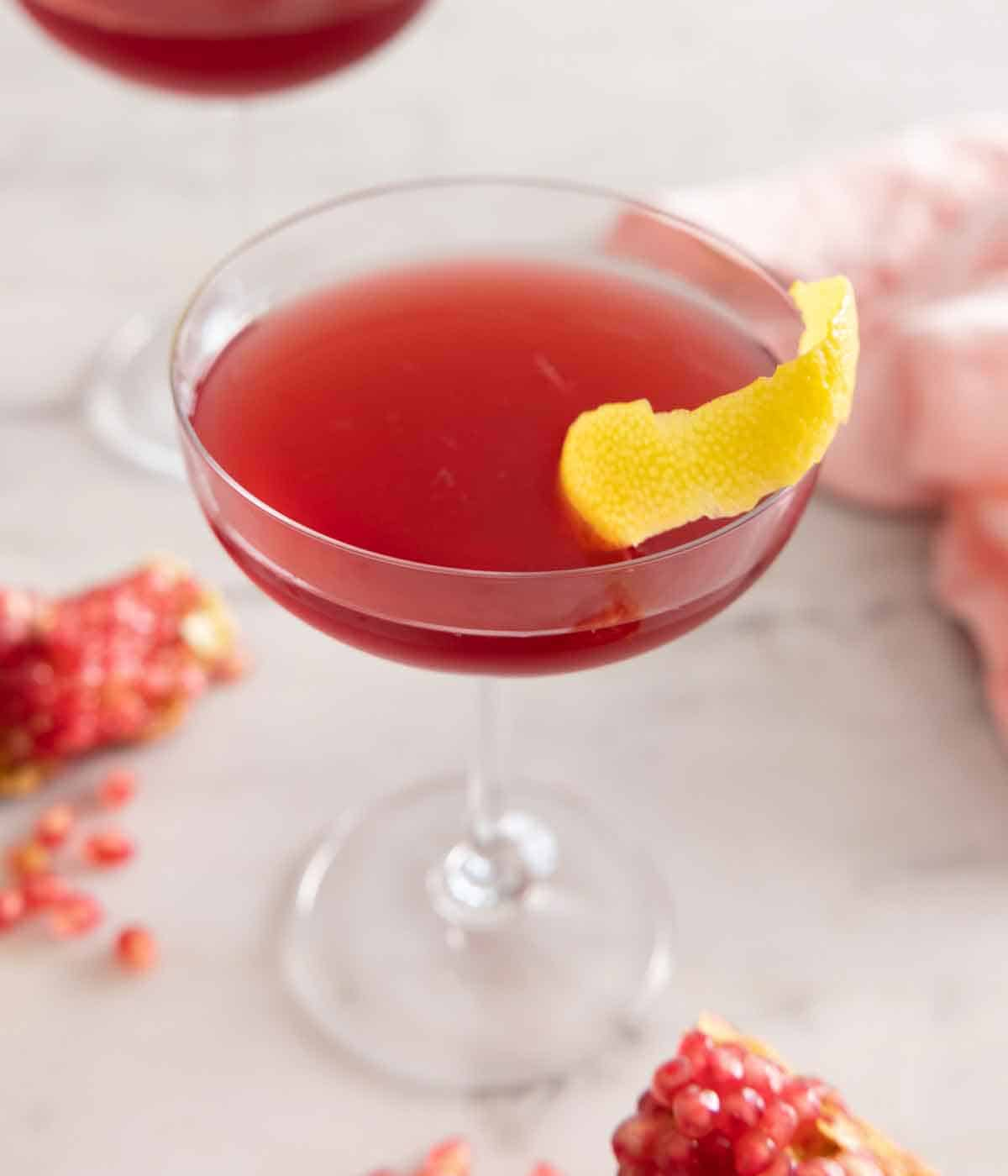 Close up of a glass of pomegranate martini with a lemon peel garnish.