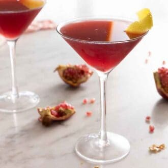 Two pomegranate martinis with fresh pomegranate segments on the counter.