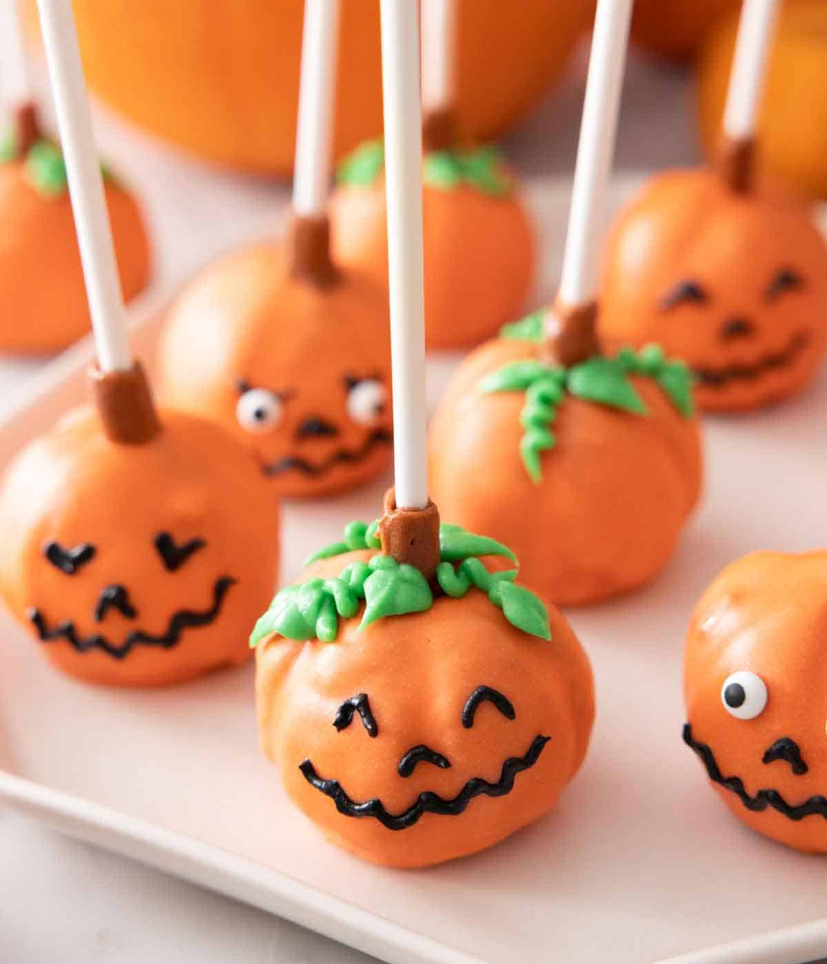 Pumpkin cake pops with smiley faces on a plate.