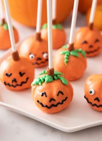 Multiple pumpkin cake pops with faces on a plate.