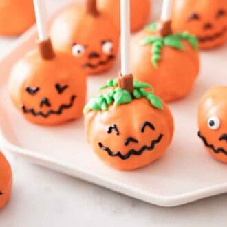 A plate with multiple pumpkin cake pops and one off to the side.