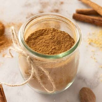 A tulip jar with pumpkin pie spice with cinnamon sticks and more spices scattered around the counter.