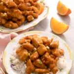 Rice and orange chicken on a plate with orange wedges in the background