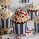 A photo of a group of red velvet cupcakes with a big dollop of cream cheese frosting.