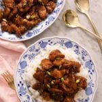 An overhead shot of Bourbon Chicken on a blue plate with rice