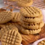 A stack of peanut butter cookies on a small wooden board