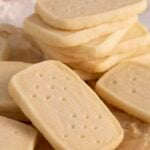 A group of shortbread cookies. some are stacked while others are on crumpled paper.