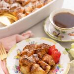 A plate with a serving of French toast casserole with sliced strawberries in front of a cup of coffee and a casserole dish.