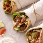 Three parchment wrapped chicken shawarma with a yogurt sauce on the side.