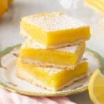 Lemon bars dusted with powdered sugar on a green and white plate.
