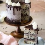 Cookies and Cream Cake on a cake stand with a piece on a plate