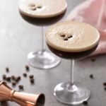 An Espresso martini on a gray surface with coffee beans scattered around