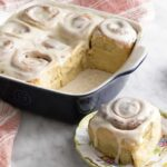 Freshly baked cinnamon rolls on a marble counter.