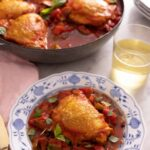 A plate with a serving of chicken cacciatore in front of a pan with more chicken.