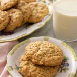 A plate with two peanut butter oatmeal cookies in front of a glass of milk and a platter of more cookies.