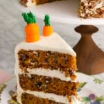 A big three layer carrot cake with a piece in the foreground.